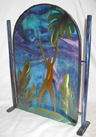 This miniature garden gate is the collaborative creation of Ochoa Stained Glass Artists and Lynn Rae Lowe of LoweCoMotion Inc., a prolific Tucson-based international sculptor working in bronze, aluminum, steel and paper. Together glass and metal can offer many full scale fine art works to adorn the exterior of your home and garden. Contact us for pricing on a custom glass and metal gate or sculpture to beautify your home exterior and garden.